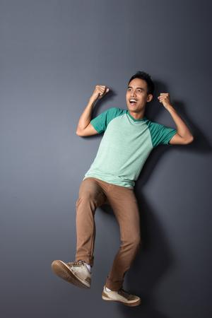 cuerpo hombre: retrato de cuerpo entero de un joven flotando y pretendiendo usar un paracaídas Foto de archivo
