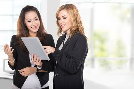 chatting: A portrait of a two young businesswoman discussion using tablet pc Stock Photo