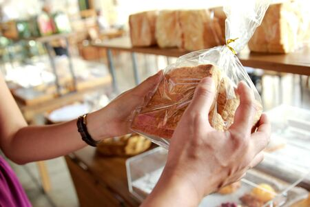 couple dating: close up portrait of hands of couple holding a pack of bread