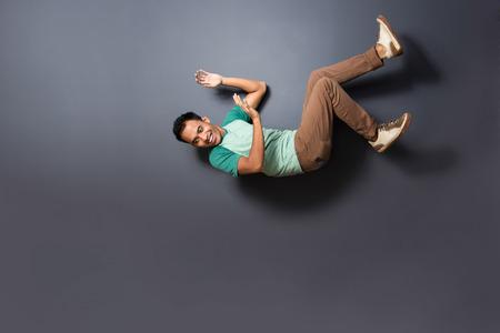 hombre cayendose: Retrato de hombre joven cayó desde la parte superior aislada sobre fondo oscuro con espacio de copia