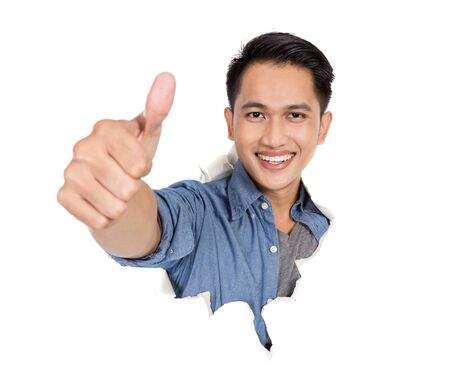 come up to: A portrait of young asian man come out from ripped of paper and showing thumb up Stock Photo