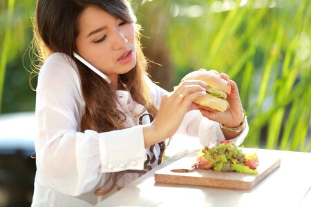 hablando por telefono: retrato de mujer multitarea hablar por teléfono mientras se come hamburguesa
