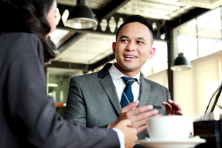 partnerships: portrait of two business people discussing new project while coffee break Stock Photo