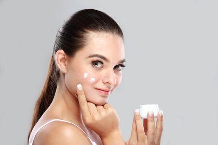 limpieza de cutis: retrato de la hermosa mujer joven y sonriente mientras se aplica un poco de crema facial en la mejilla, con copia espacio