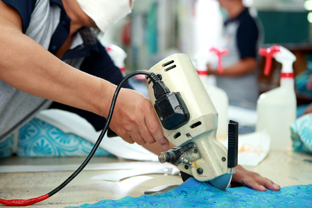 precisely: portrait of worker using cutting machine for cutting fabrics at textile factory Stock Photo