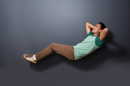 levitation: portrait of a handsome man floating with sleeping pose isolated on dark background