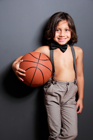 long pants: portrait of cute little boy with long hair smiling and holding a basketball