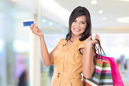 Een portret van happy Aziatische vrouw met boodschappentassen en een creditcard Stockfoto