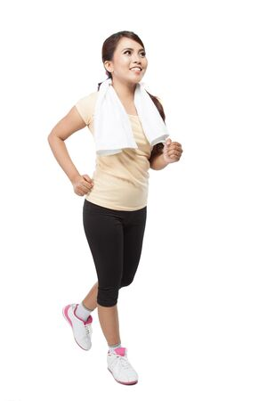 A portrait of a beautiful young asian woman jogging indoor, isolated over white background