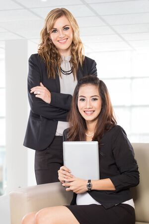 well dressed girl: A portrait of two young businesswoman sitting and standing next to each other, smiling. Isolated.