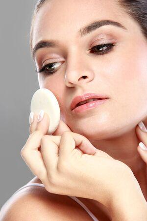 powder puff: close up portait of beautiful caucasian model applying some powder using powder puff Stock Photo