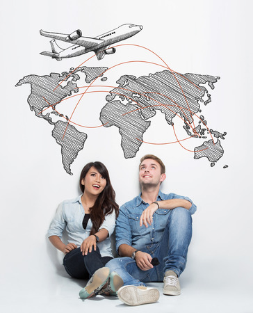mixed race: A portrait of happy young mixed race couple sitting on the floor together and imagining to have trip around the world