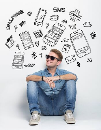 people looking up: A portrait of Young caucasian man wear sunglasses while sitting on the floor thingking about having a new smartphone