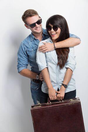 valise voyage: Un portrait d'un jeune mâle caucasien souriant tout en donnant sa petite amie asiatique un backhug