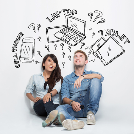 young woman: A portrait of mixed race couple thinking about having between cellphone, laptop or tablet Stock Photo