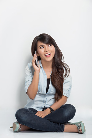 beautiful girl: A portrait of young woman sitting on the floor while calling with her smartphone Stock Photo