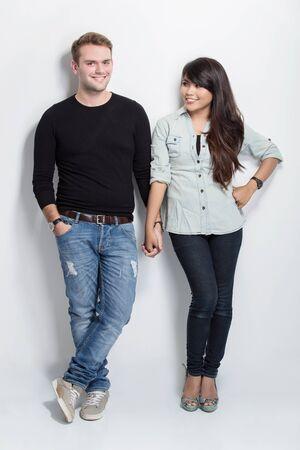 couple mixte: Un portrait d'un couple de la main tenue permanente mixte tout en se penchant sur fond blanc Banque d'images