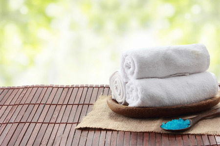 A portrait of Rolled towel in a tray, spa concept