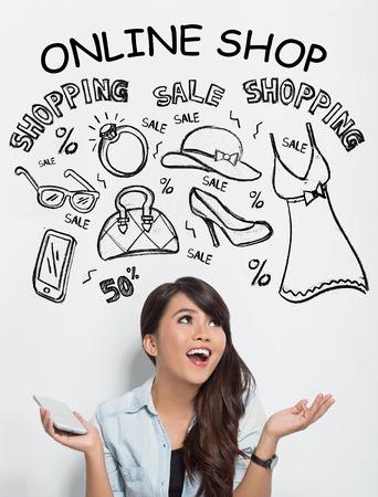 Un retrato de la hermosa mujer asiática sosteniendo un telefono mientras imaginando acerca de las compras en línea