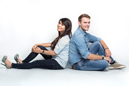 A portrait of happy young Mixed race couple sitting back to back on the floor Stock Photo - 42855816