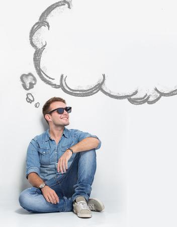 젊은 백인 남자의 초상화 뭔가 [NULL]에 대해 생각하는 바닥에 앉아있는 동안 선글라스를 착용하십시오. 거품 스피치로 copyspace