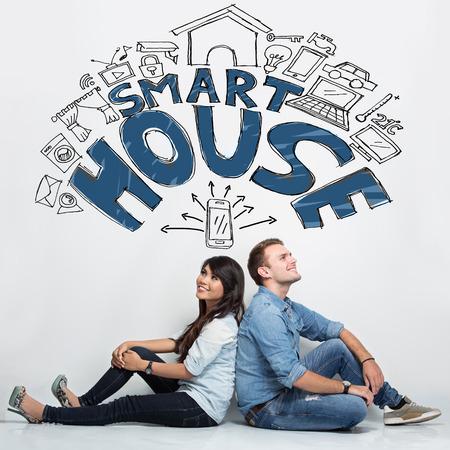 caja fuerte: Un retrato de una pareja de raza mixta Imaginating sobre el sistema de casa inteligente, cosas ilustrados Foto de archivo