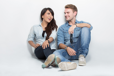 young happy couple: A portrait of happy young mixed race couple sitting on the floor embracing
