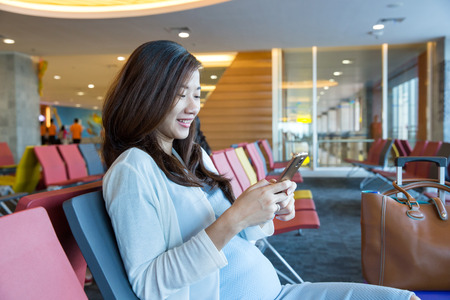 Woman in the aiport lounge sitting in chair by the window and using a mobile phone for checking her flight details with wifi connection