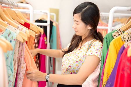 woman clothes: portrait of young beautiful asian woman shopping in clothing store