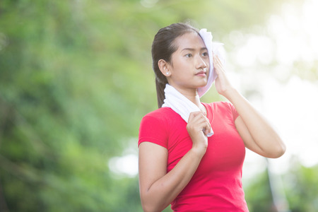 A portrait of an Asian woman wiping her sweat after exercise Stock Photo
