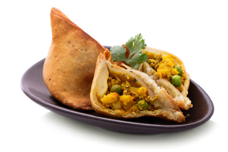 portrait of delicious sliced indian samosa isolated on white background
