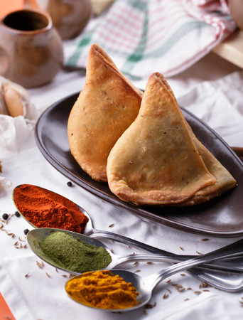 samosa: portrait of indian samosa with spices on the spoons