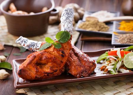 tandoori chicken: close up portrait of indian tandoori chicken garnished