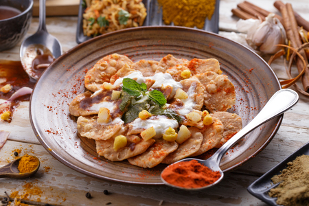 chaat: full portrait of indian streetfood papri chaat garnished and served with yoghurt