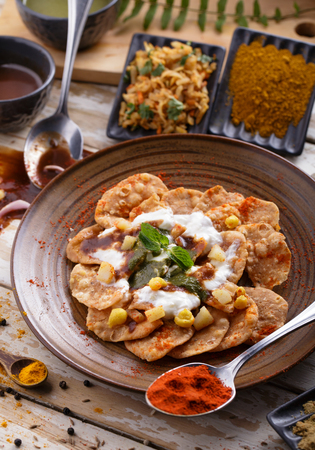 chaat: portrait of indian snack papri chaat served with yoghurt with seasoning
