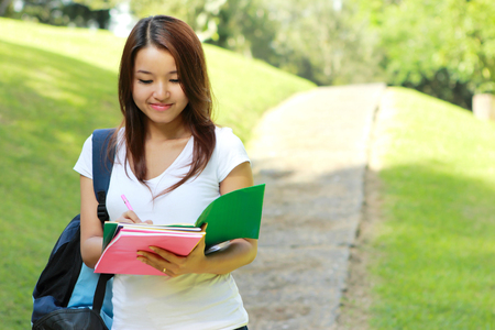 students: portrait of college student studying while walking at college park with copy space