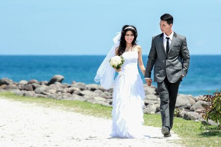 full body portrait of romantic newlywed couple holding hand and walking at seashore in sunny day