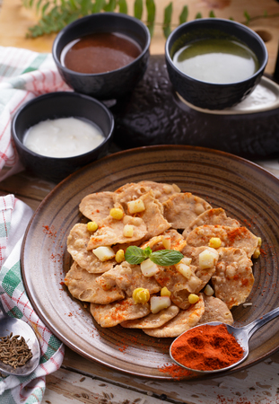 sauces: portrait of indian snack papri chaat with sauces and yoghurt