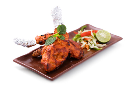 delicious, indian tandoori chicken served with salad isolated on white background