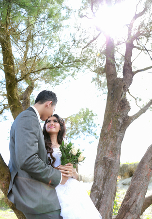 lean back: portrait of romantic newlywed couple lean back on tree in sunny day