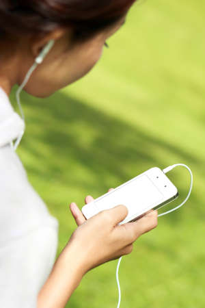 mobilephone: close up portrait of a woman listening a music in mobilephone using earphone
