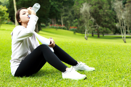 get a workout: portrait of sporty woman sitting and get refreshment after workout with copy space