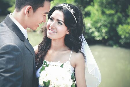 happy smiling: portrait of beautiful bride and handsome groom staring each other with copy space