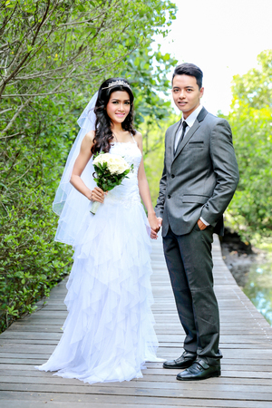cuerpo completo: full body portrait of beautiful bride and handsome groom smiling and holding each other hands
