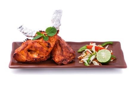 tandoori chicken: portrait of indian tandoori chicken served with salad isolated on white background