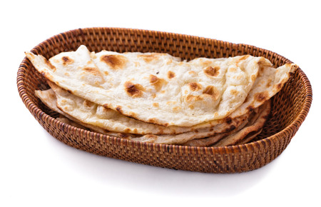 stack of indian naan bread in small basket isolated on white background Foto de archivo