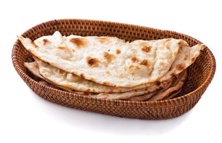 stack van de Indiase naan brood in kleine mand op een witte achtergrond