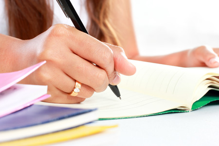 article writing: close up portrait of human hands writing on notebook using ballpoint Stock Photo