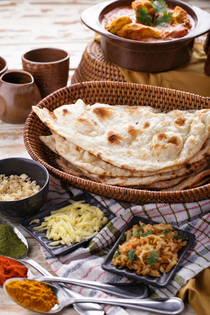 naan: portrait of indian naan bread with chicken curry and some ingredients Stock Photo
