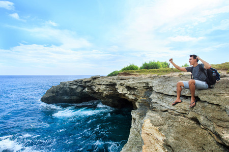 express feelings: portrait of a man sitting at the edge of cliff express his feelings while looking at the blue sea
